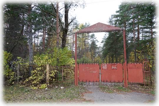 Ржавые ворота аккуратно закрыты на цепь. За ними — люди, слишком похожие на охранников